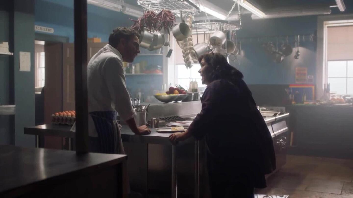 "A man and woman speak to each other in a kitchen. | ""Delicious"""