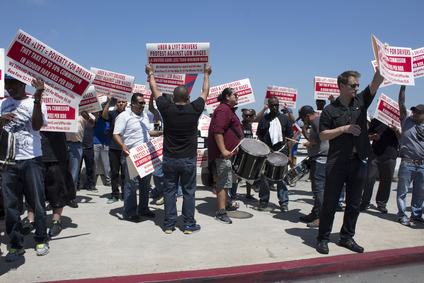 LAX Rideshare Protesters hold signs curbside