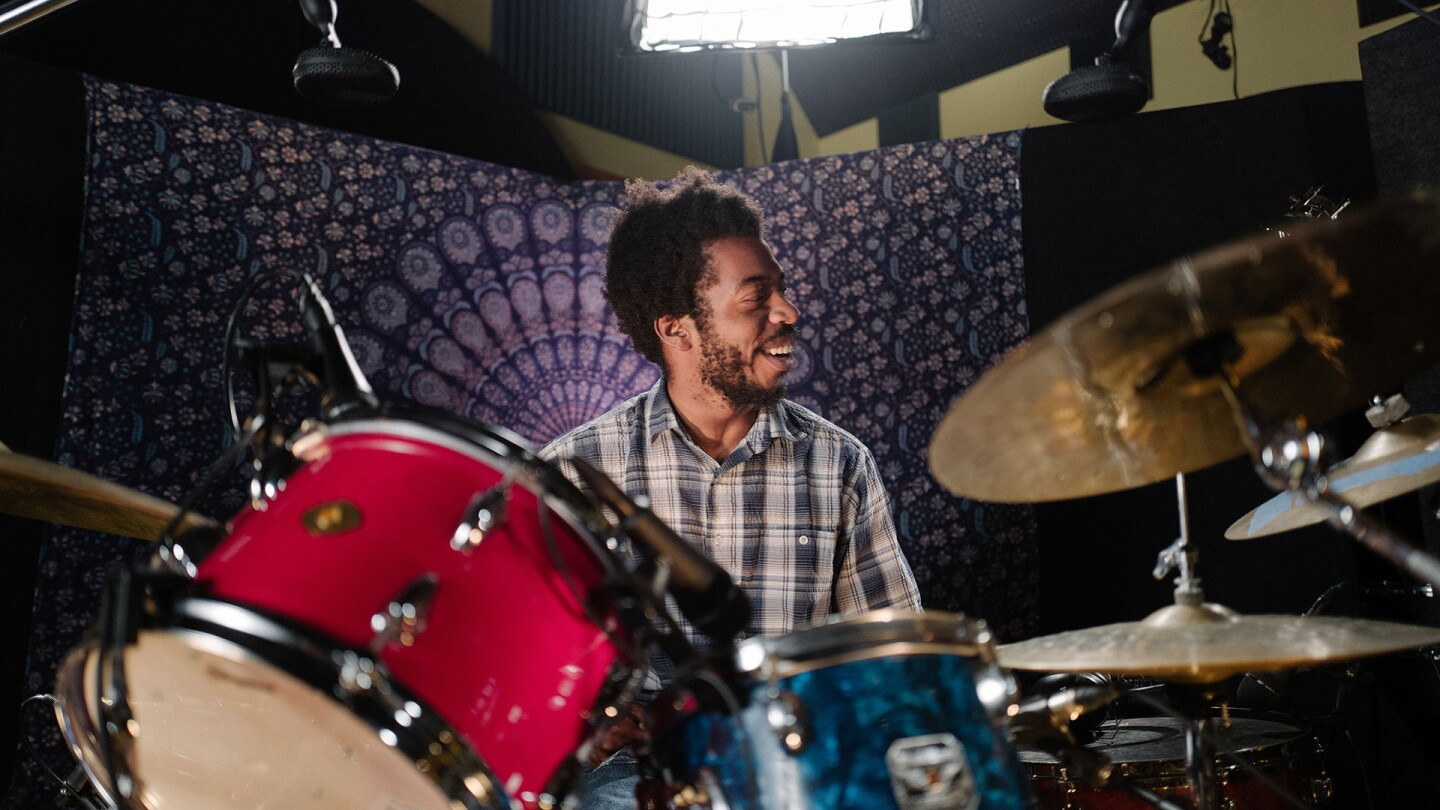 """Mekala Session playing drums with a purple background 