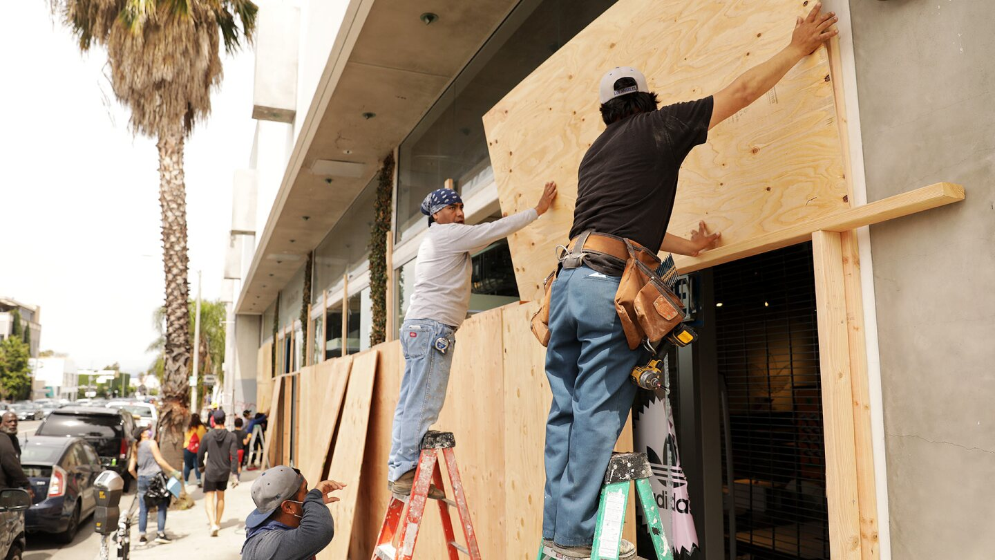 Workers board up the Adidas store on Melrose Avenue on Sunday, May 31, 2020. | Christina House / Los Angeles Times via Getty Images