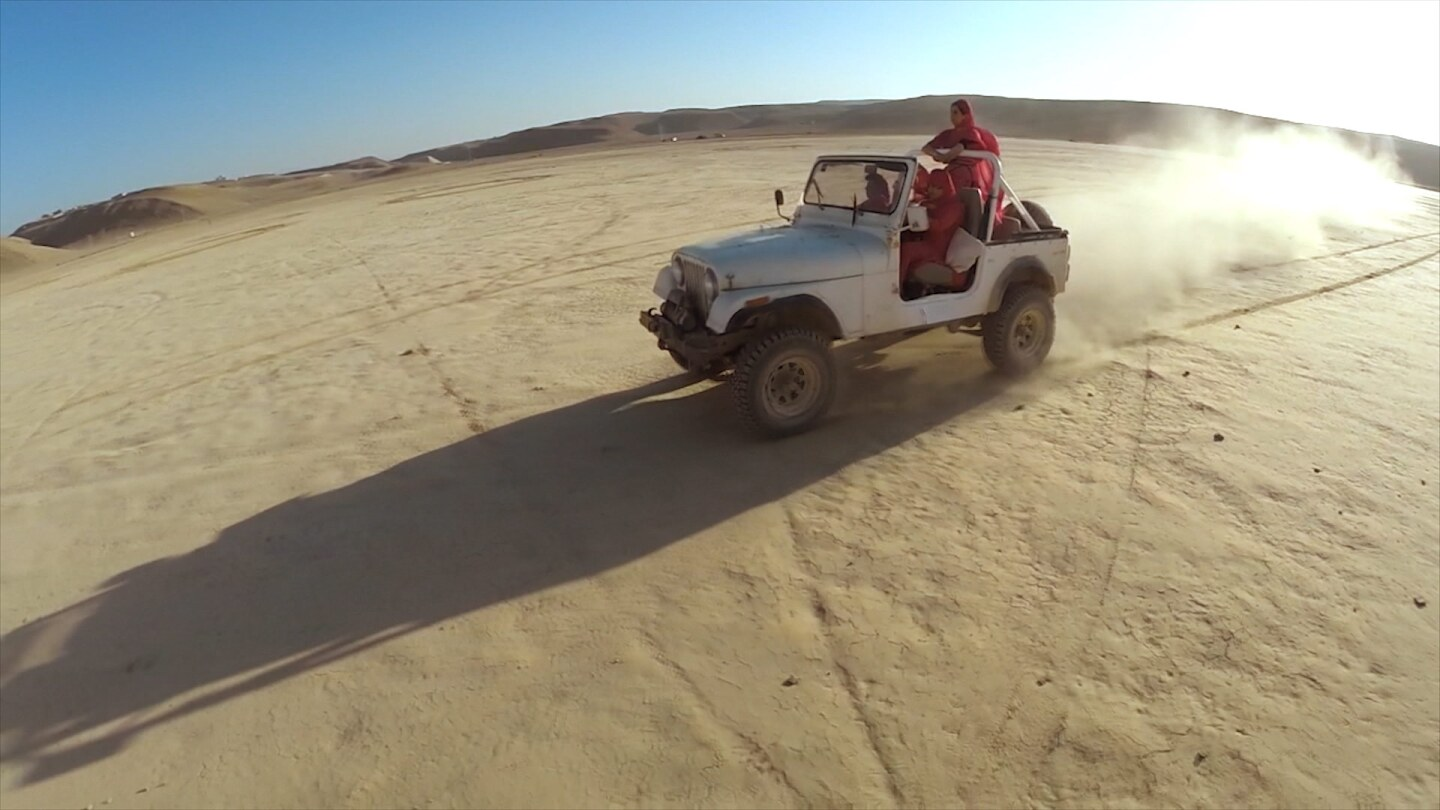 Still from S05E02 of Border Blaster: A white wrangler with women in red outerwear crosses the desert.