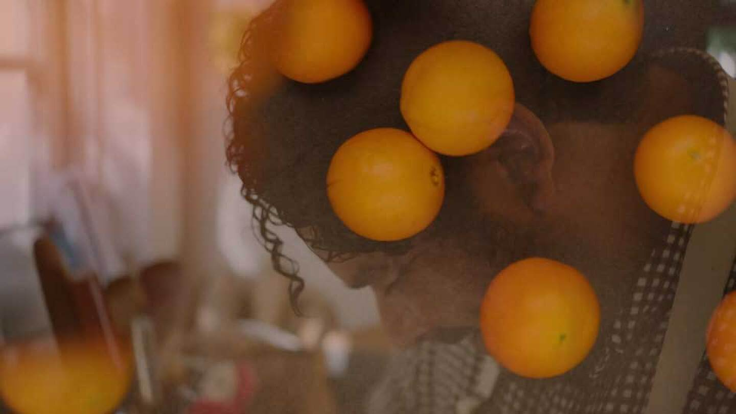 "A man in profile interlaced with falling oranges |  | Still from ""Artbound"" Current:LA"