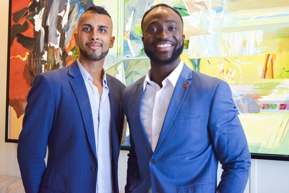 Two young Black men in suits pose together and smile at the camera.