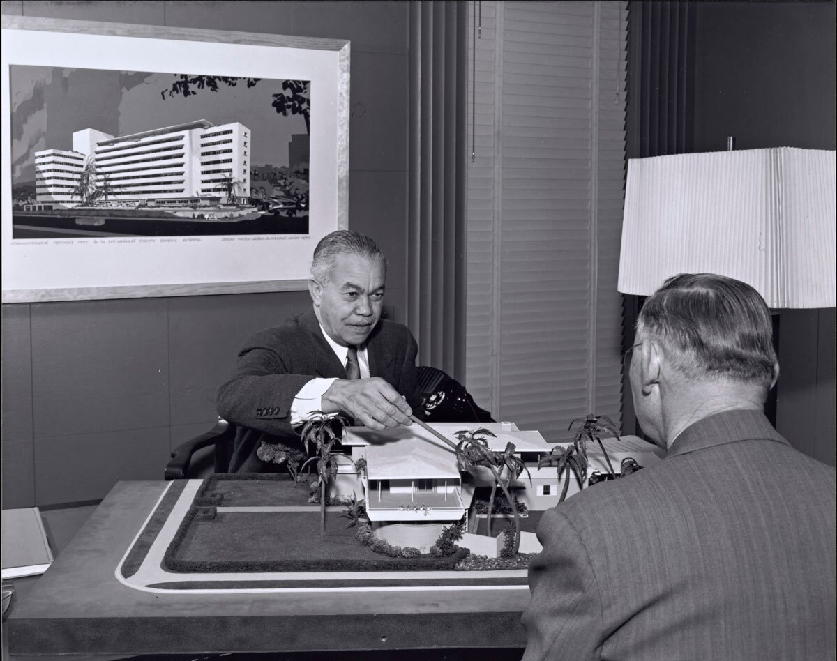 Paul R. Williams on the other side of the desk showing plans   J. Paul Getty Trust. Getty Research Institute, Los Angeles