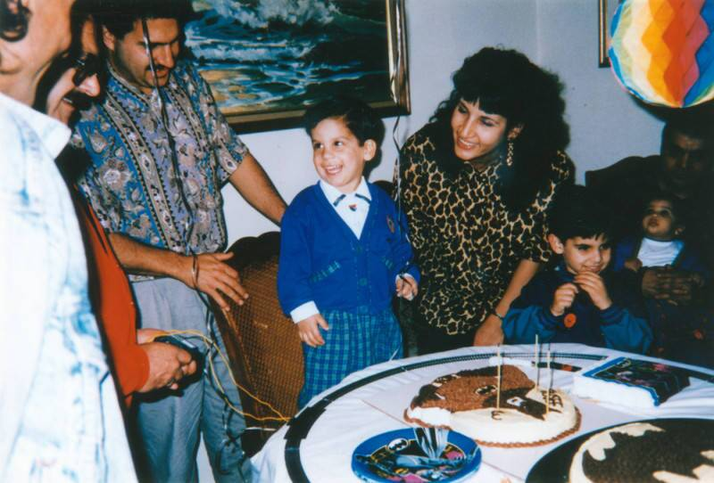 A little boy smiles at his family at his birthday party, circa 1994