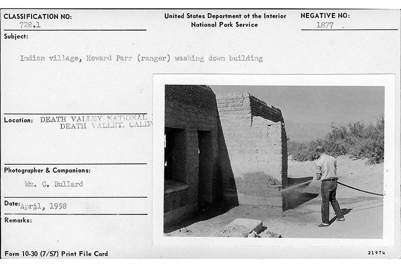 Park Ranger Howard Parr washes down a Timbisha Shoshone adobe house, April 1958.