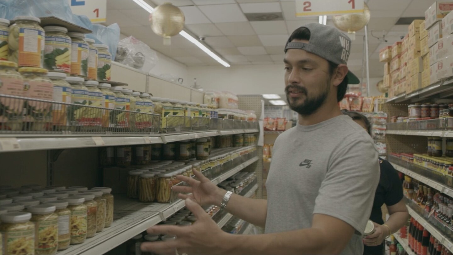 "Louis Tikaram of EP/LP showing Bangkok Market products | Still from ""The Migrant Kitchen"" Louis and Jazz"