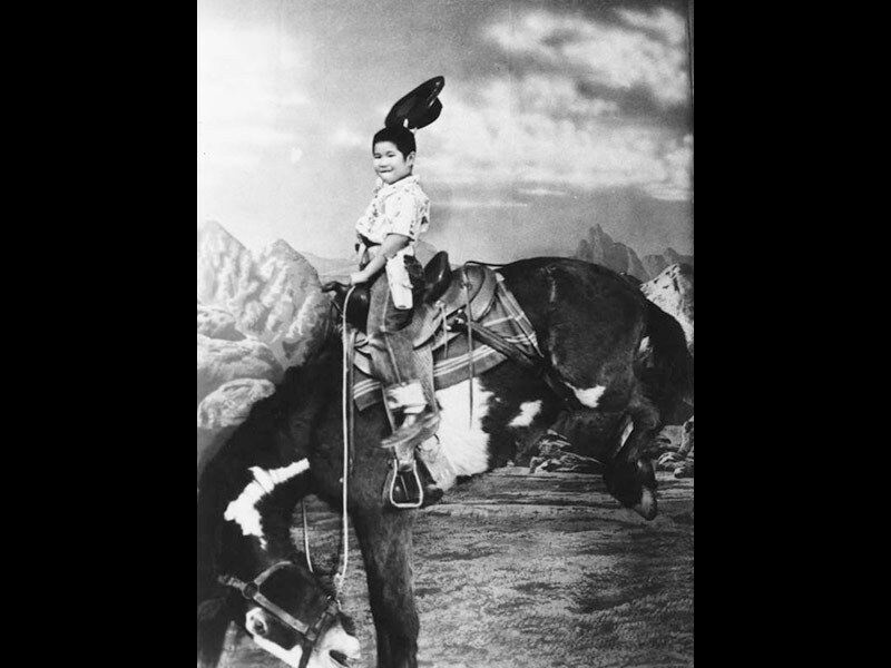 Black and white photo of a small Chinese American boy riding on a simulated bronco.