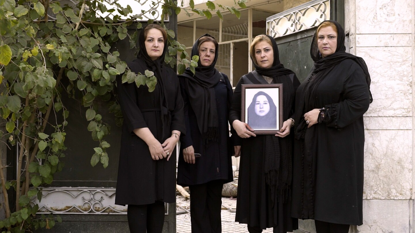 Four women wearing black pose for a photo, with one of them holding a framed portrait of another woman.