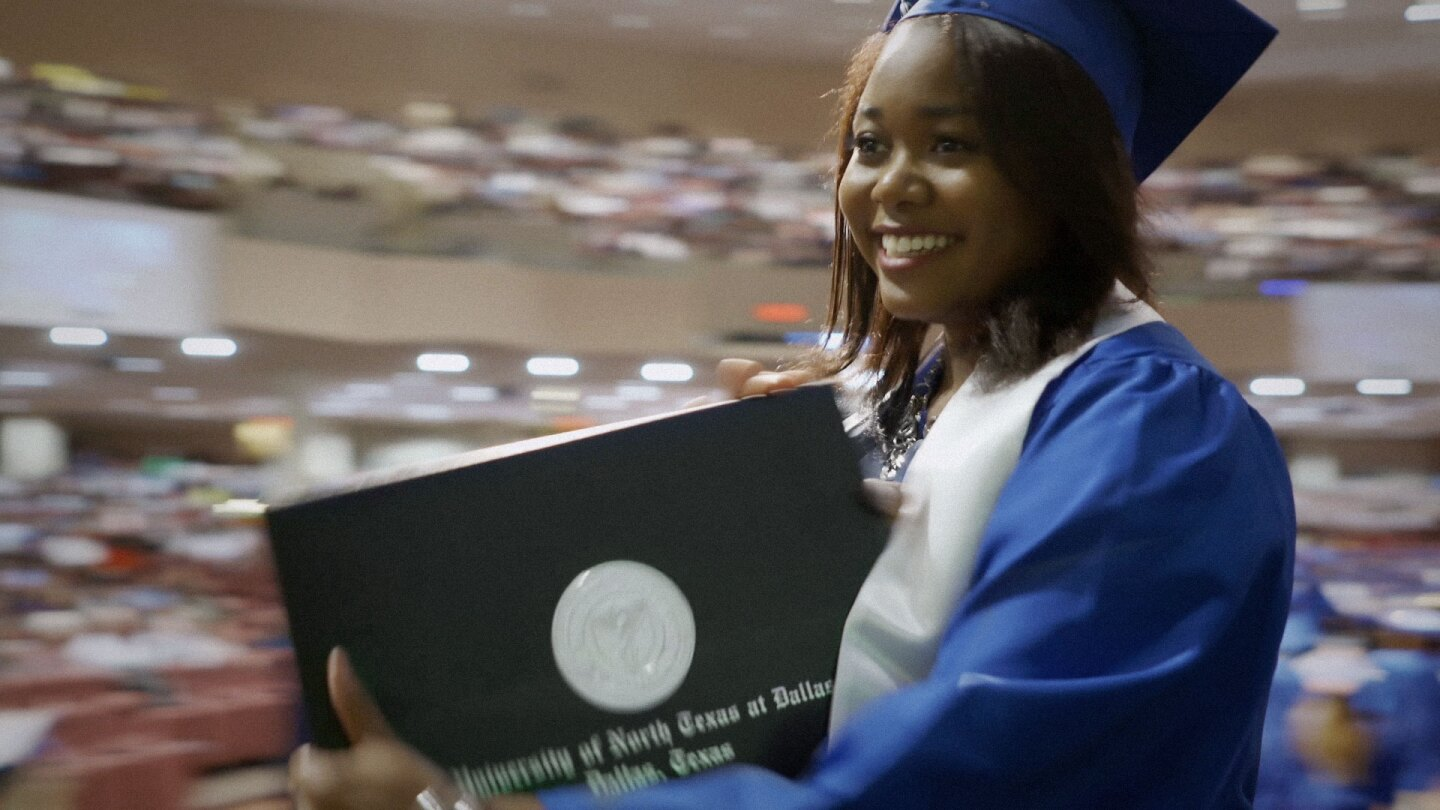"""Woman receiving a diploma at graduation ceremony. 