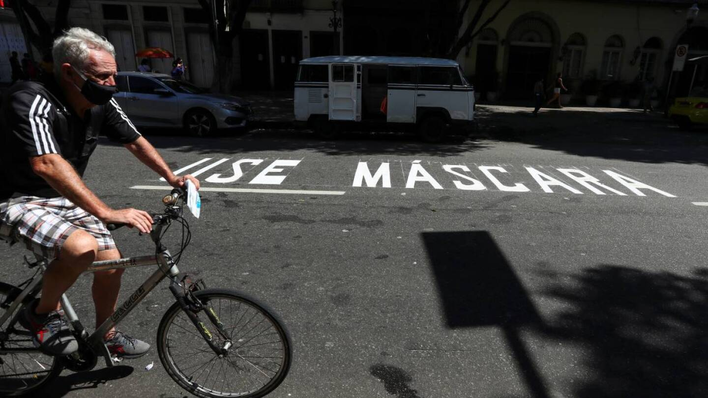 "A man rides a bicycle next to a message reading ""Use mask"" painted on the street, following the coronavirus disease (COVID-19) outbreak, in Rio de Janeiro, Brazil April 30, 2020. 