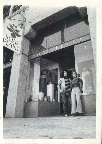 """An archival black and white photo of Billy Shire and his mother, Barbara Shire, standing in front of their family-store, Soap Plant. The store has a glass storefront with the words """"SOAP PLANT"""" written across and a store sign reading the same thing."""