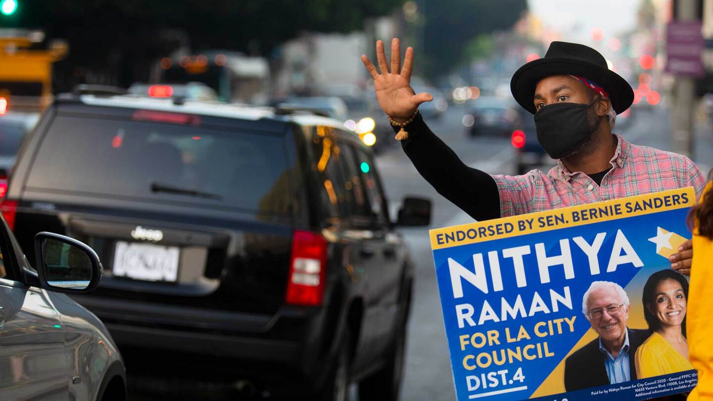 A man holds up a vote sign for Nithya Raman on Tuesday, Nov. 3, 2020 in Los Angeles, CA. | Francine Orr / Los Angeles Times / Getty Images