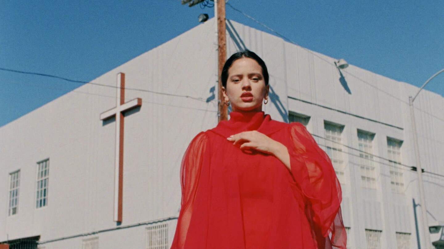 "Still from ""De Plata:"" Rosalía appears in red in front of a church."
