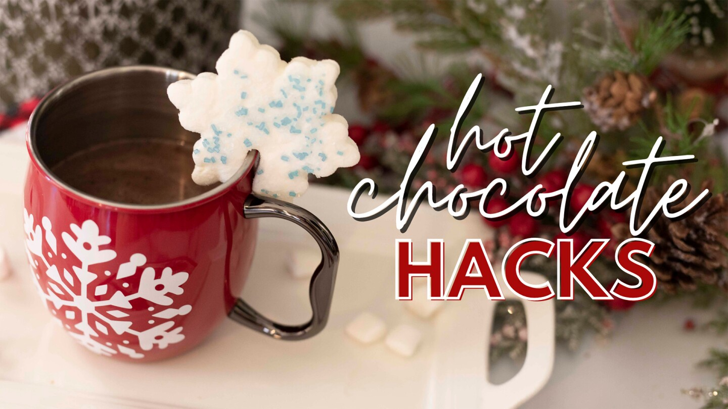A mug of hot chocolate with a snowflake-shaped cookie wedged on the side.