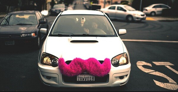 A Lyft driver waves for the camera.