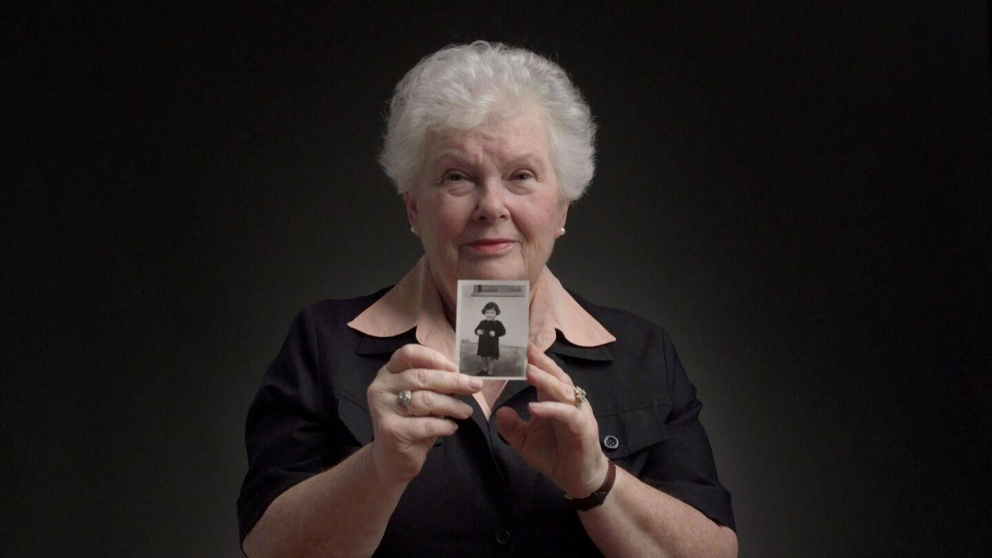 "A Holocaust survivor holds up a picture of herself as a toddler. | ""The Windermere Children: In Their Own Words"""