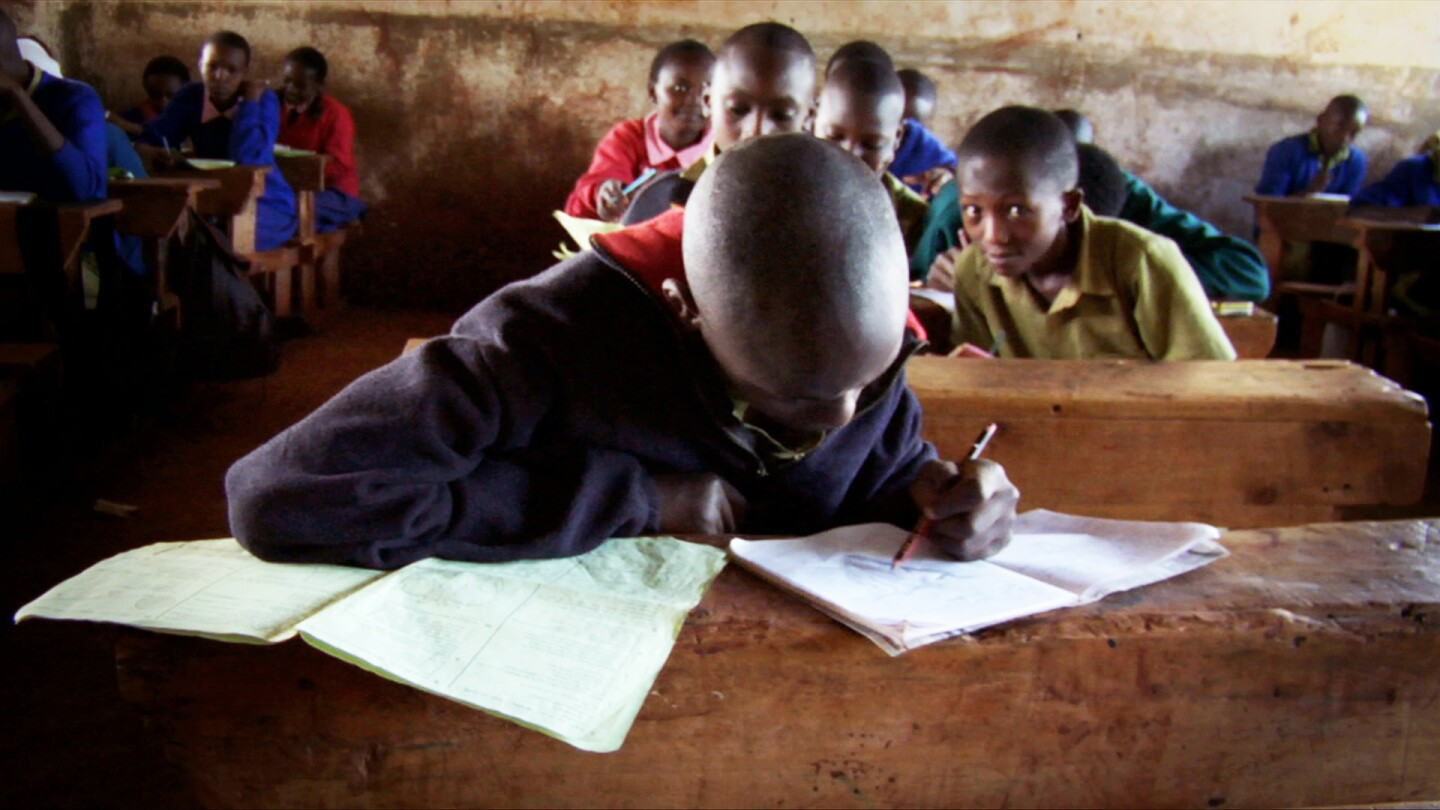 A student concentrates on writing in a notebook at his desk.