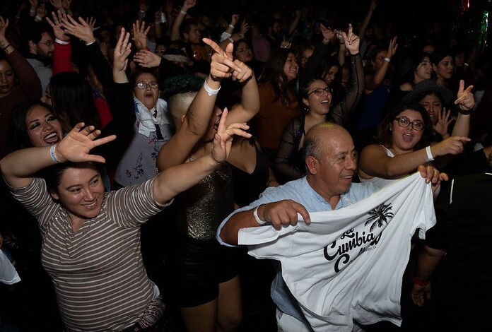 "A crowd dances at the Cumbiaton Posada Tropical event December 28, 2020. A man in the foreground holds up a white t-shirt that reads, ""Cumbia."""