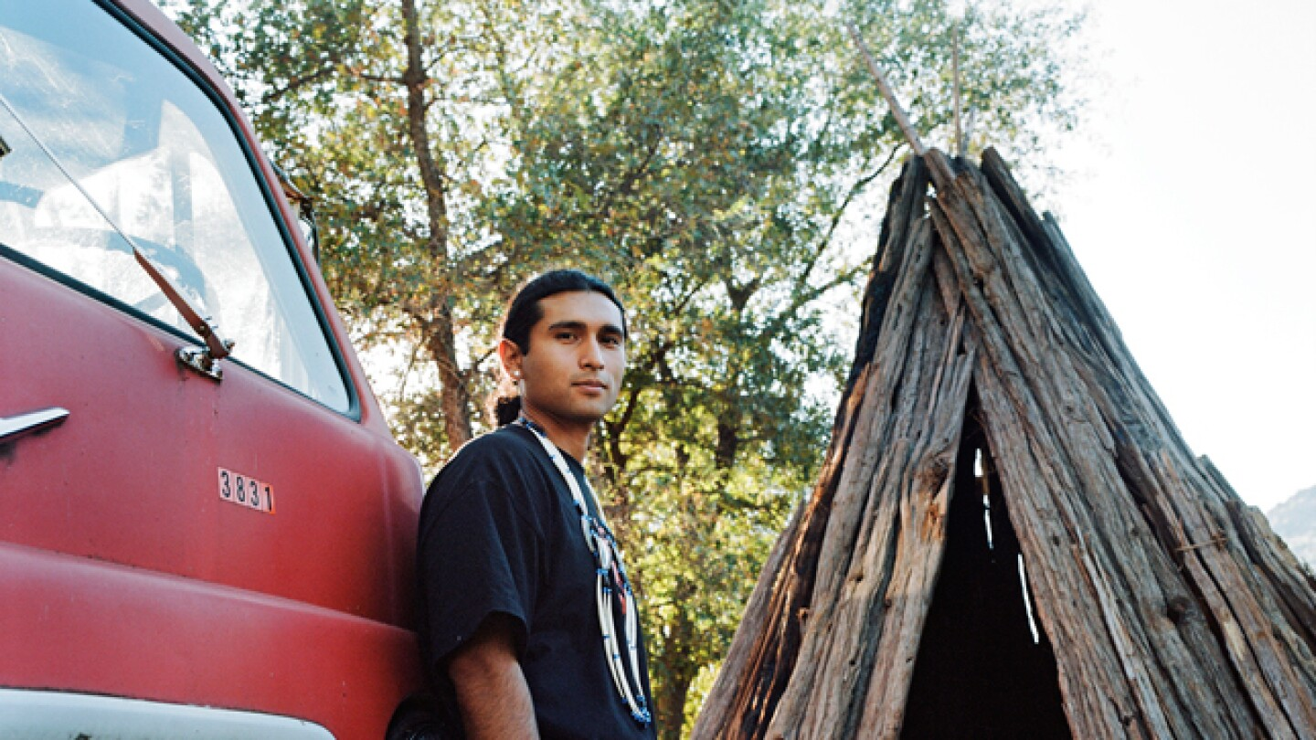 Michael Preston poses next to wooden hut and a red car.