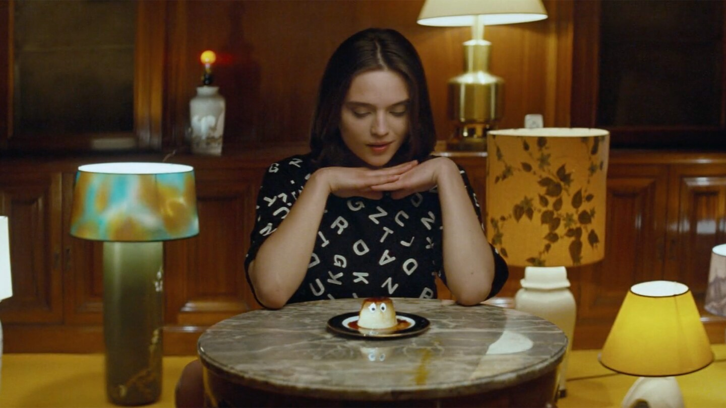 Still from Creme Caramel: A woman in a room with many lamps looks down at a creme caramel that has eyes.