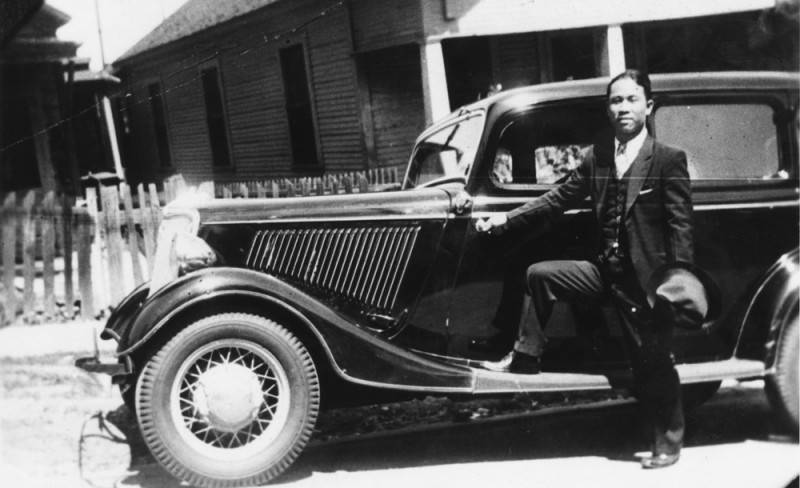 Black and white photograph of a Japanese American man in a suit posing with a car, circa 1935