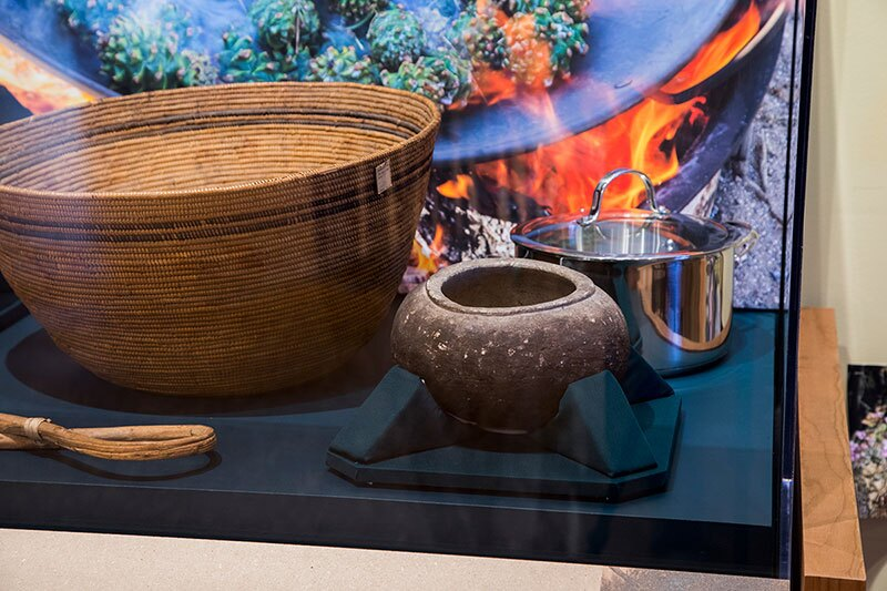 a Gabrielino/Tongva cooking basket and a Paiute cooking stick (just visible at the lower right), both from the early 20th century, and a Gabrielino/Tongva cooking bowl, sit beside a stainless steel cooking pot. Photo: The Autry Museum