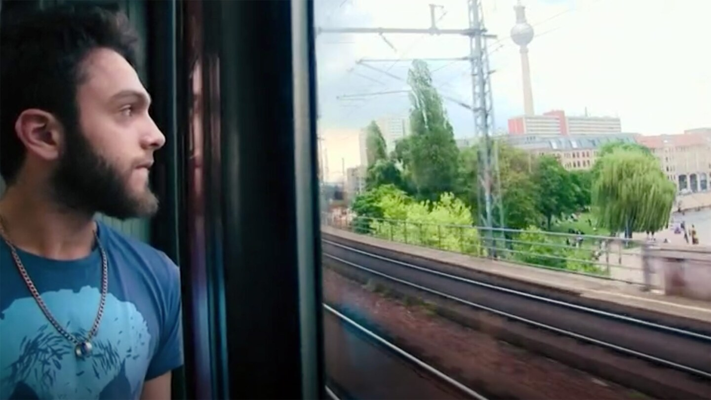 A young man looks out of a train window