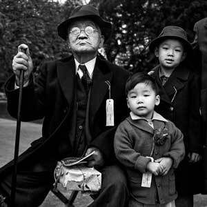 """Shigeo """"Jerry"""" Aso, 3, center, and his brother, Sadao """"Bill"""" Asano, 6, with their grandfather, Sakutaro Aso, 70, as they wait for a bus to take them to Tanforan Assembly Center.   Courtesy UC Berkeley Bancroft Library, War Relocation Authority Photographs"""