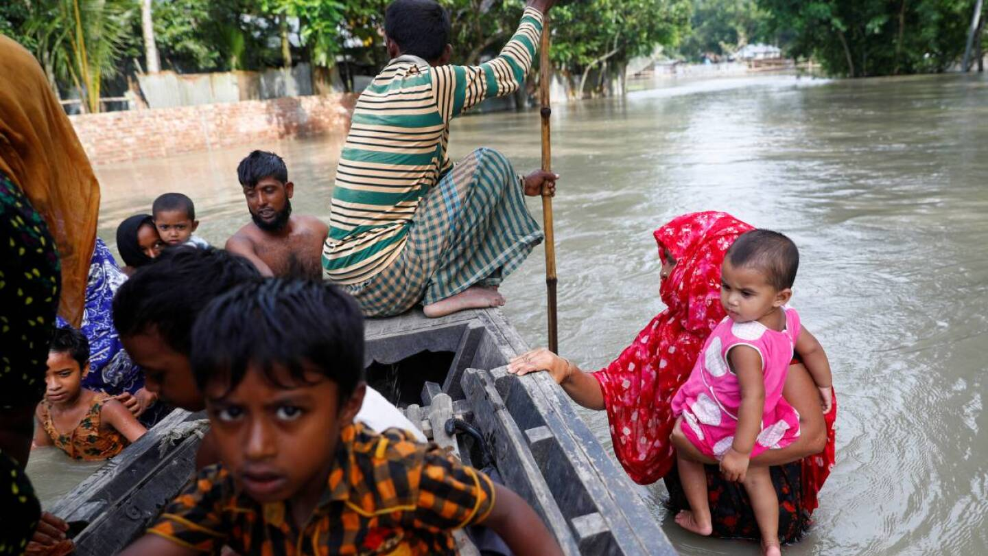 Flood-affected people get on a boat to cross a stream in Jamalpur, Bangladesh, July 18, 2020. | REUTERS/Mohammad Ponir Hossain