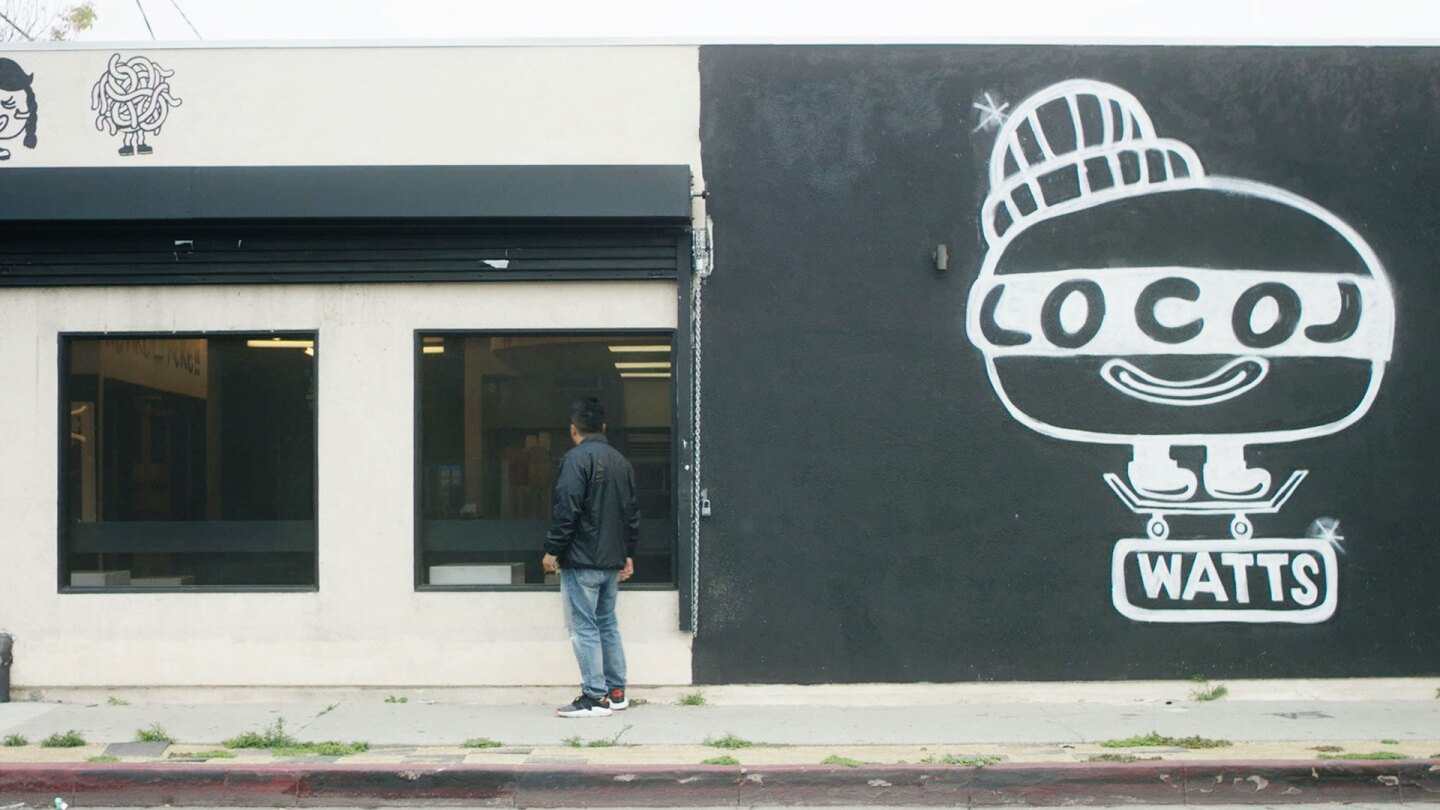 "Roy looks into the window of his establishment Locol in Watts. | Still from ""Broken Bread"""