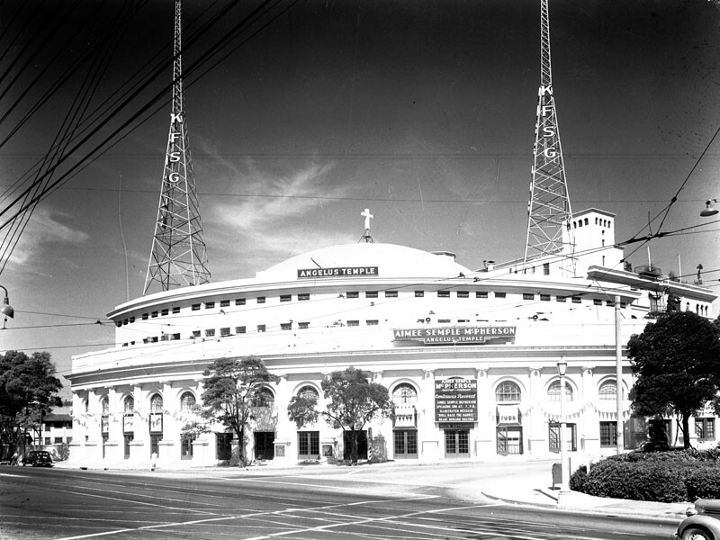 Aimee Semple McPherson's Angelus Temple, twin towers on the roof, drew thousands of congregants to weekly services and tens of thousands more to listen her radio broadcasts.
