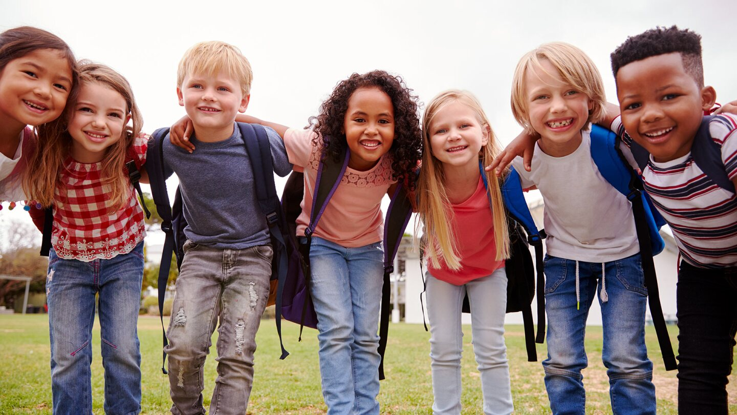Seven small children of different skin tones huddle together and smile at the camera. iStock