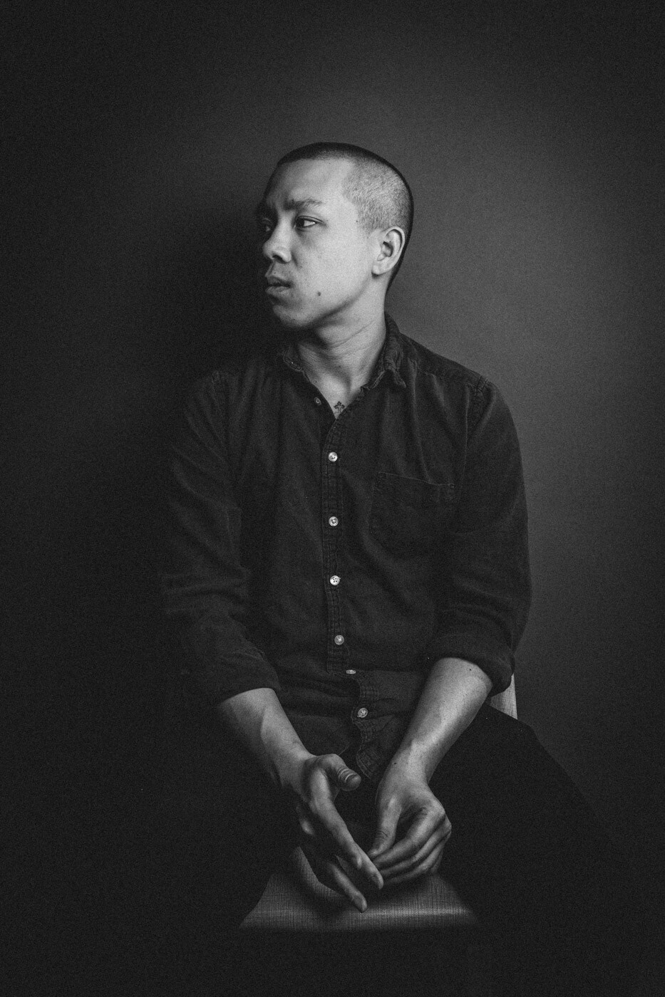 A black and white portrait photo of Chef Jon Yao of Kato taken from the knees up. He wears a dark-colored button-up shirt and looks to the side.