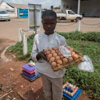 Moses, 10, sells eggs outside a petrol station to support his family. Child rights organisations say they are seeing a rise in child labour during the coronavirus pandemic. Photo taken on June 22, 2020, in Gulu, northern Uganda. Sally Hayden/Thomson Reute
