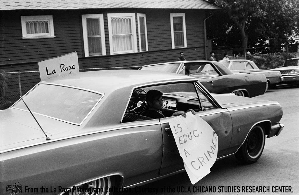 CSRC_LaRaza_B1F3C2_DW_002 Man holds a sign in his car during the Roosevelt High School walkouts | Devra Weber,  La Raza photograph collection. Courtesy of UCLA Chicano Studies Research Center