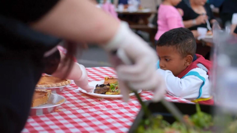 "A young boy enjoys food served at Bracken's food truck.   Still from ""Broken Bread"""