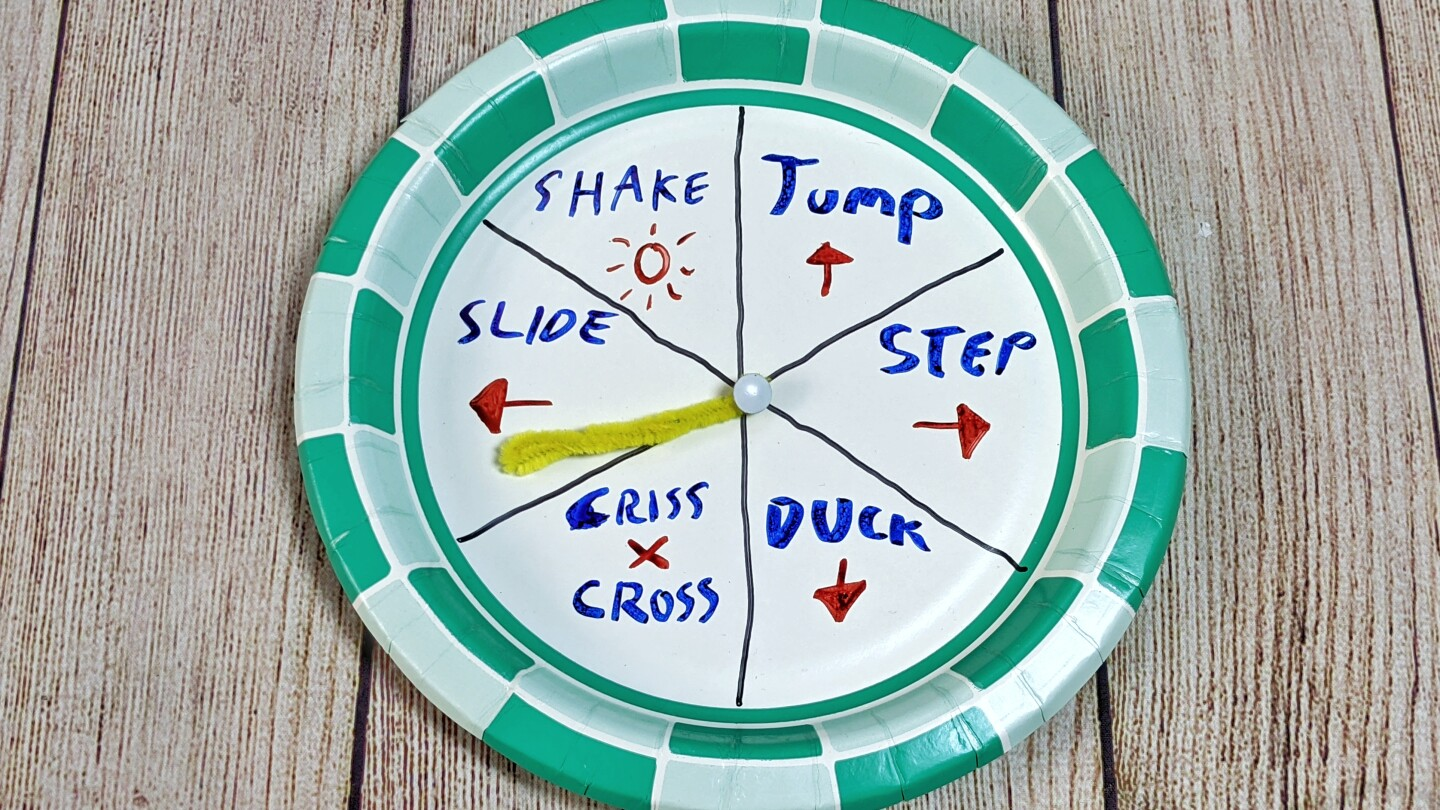 A paper plate spinner is divided and marked with instructions like step to the right, jump and duck.