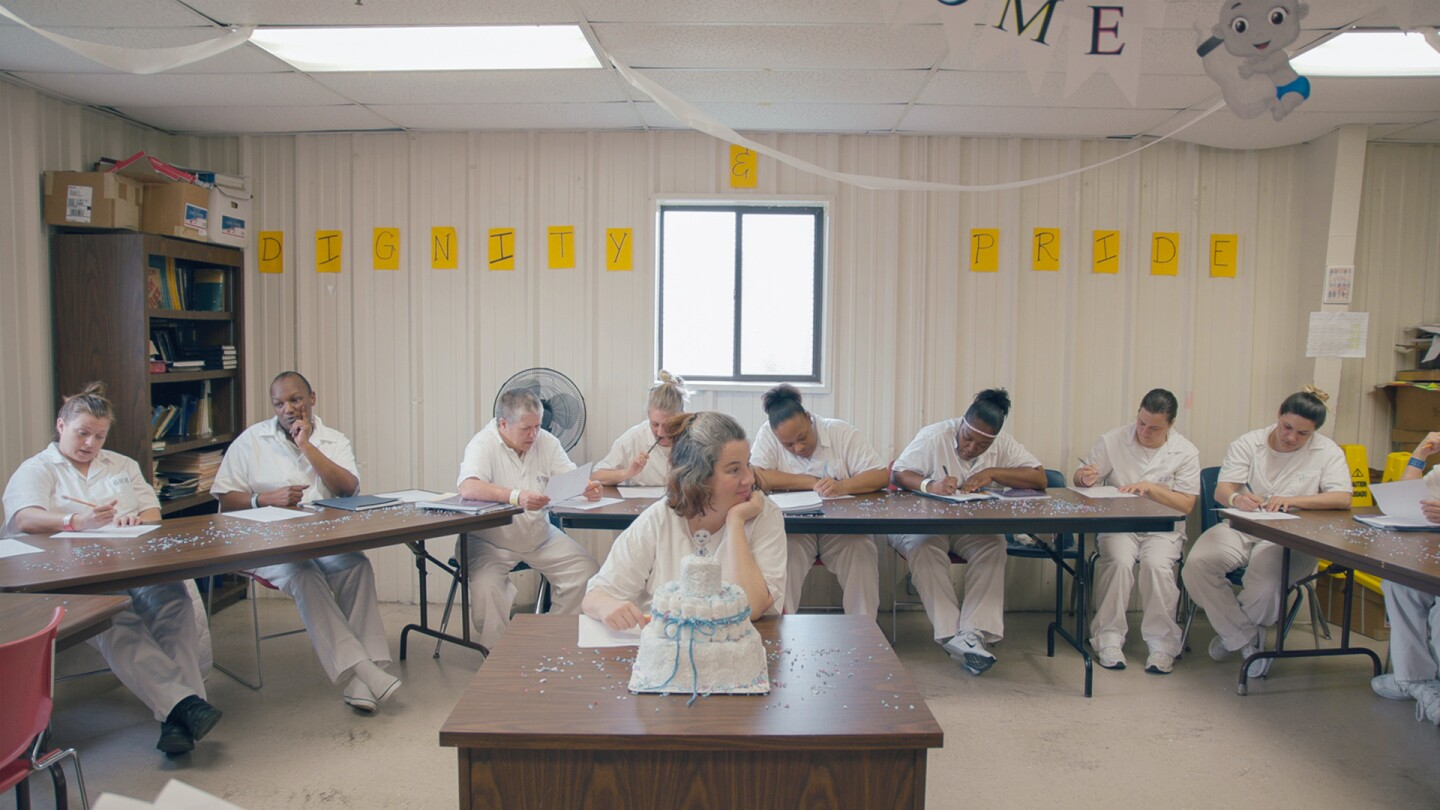 "Pregnant inmate Misty sits in the center of a room with a cake celebrating her soon newborn baby in front of her, with fellow inmates sitting around her writing on pieces of paper. | From ""America ReFramed: Tutwiler"""