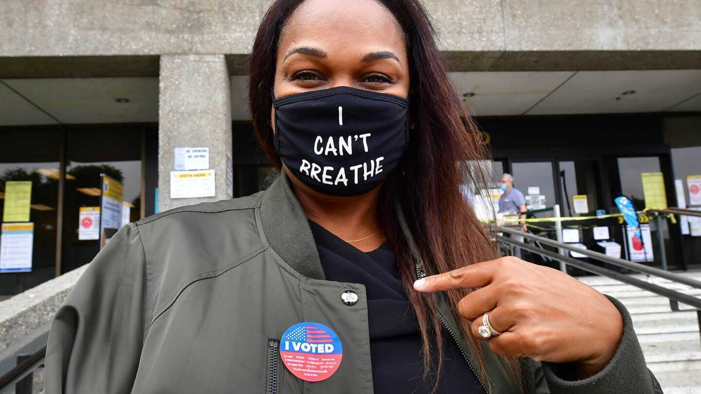 """Tonya Swain points to her """"I Voted"""" sticker after casting her vote in the 2020 US elections at the Los Angeles County Registrar in Norwalk, CA."""