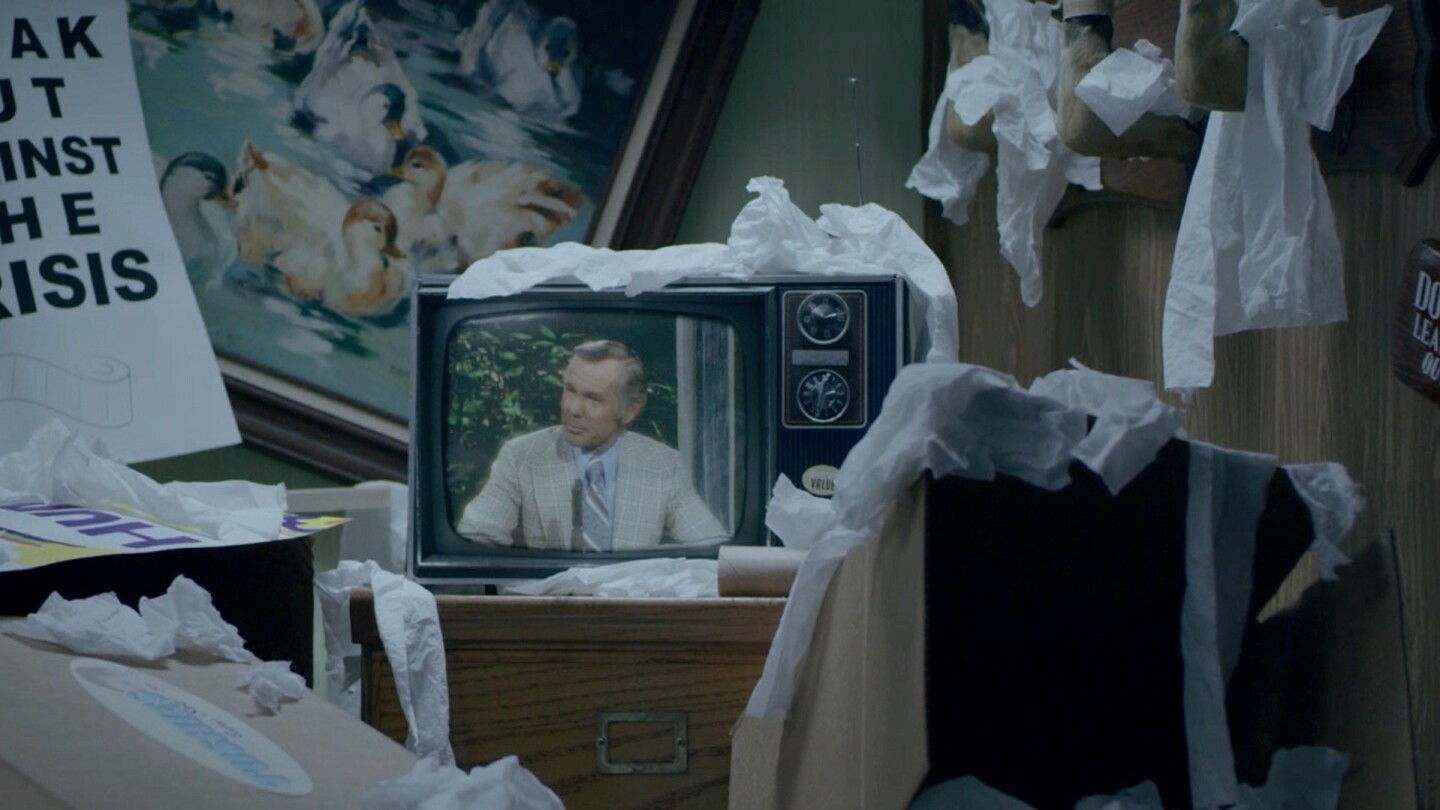 "A television screen with Johnny Carson is set against a room full of signs in a still from ""Out of Stock"" 