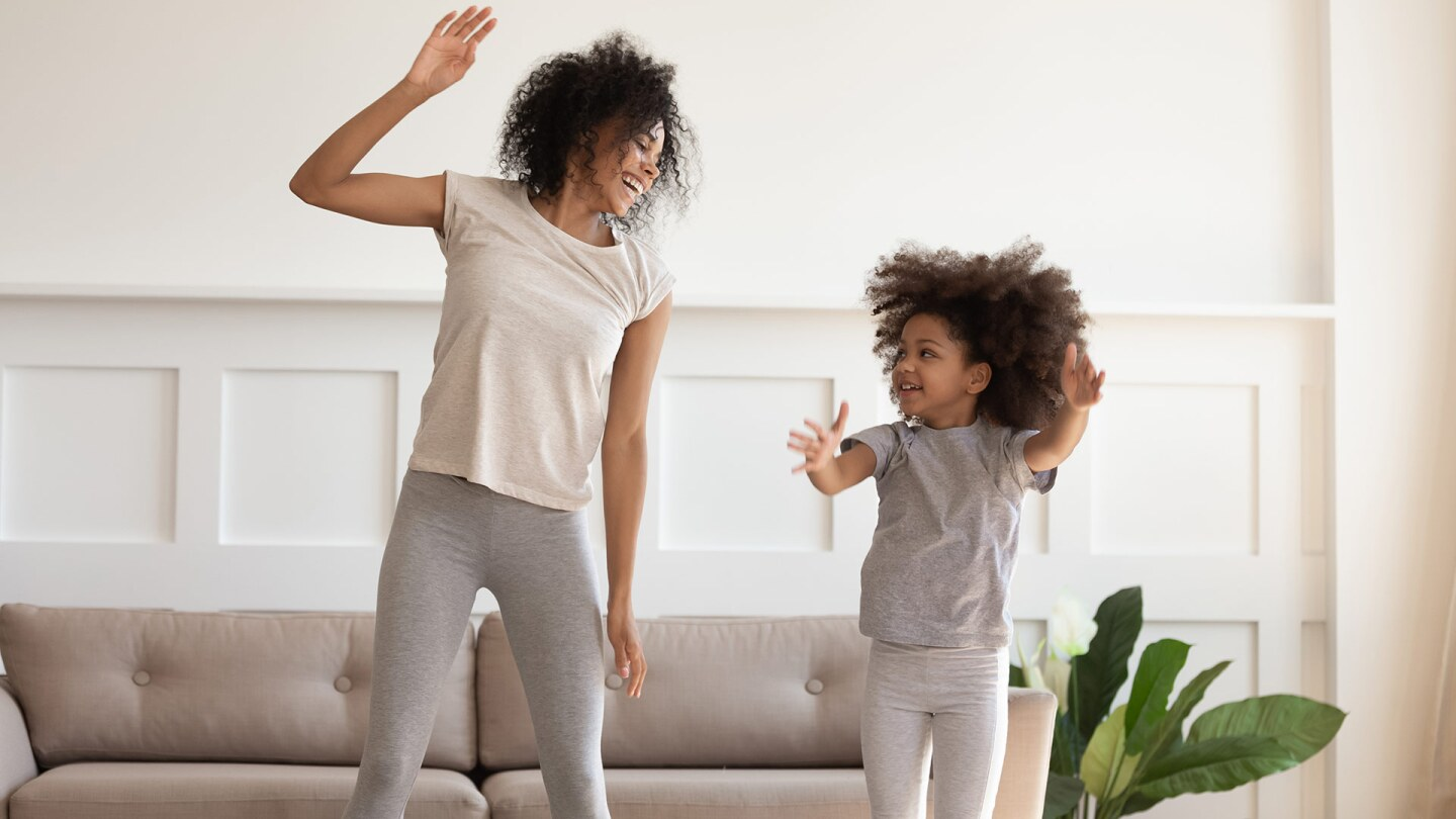 A woman and a little girl jump together as they dance