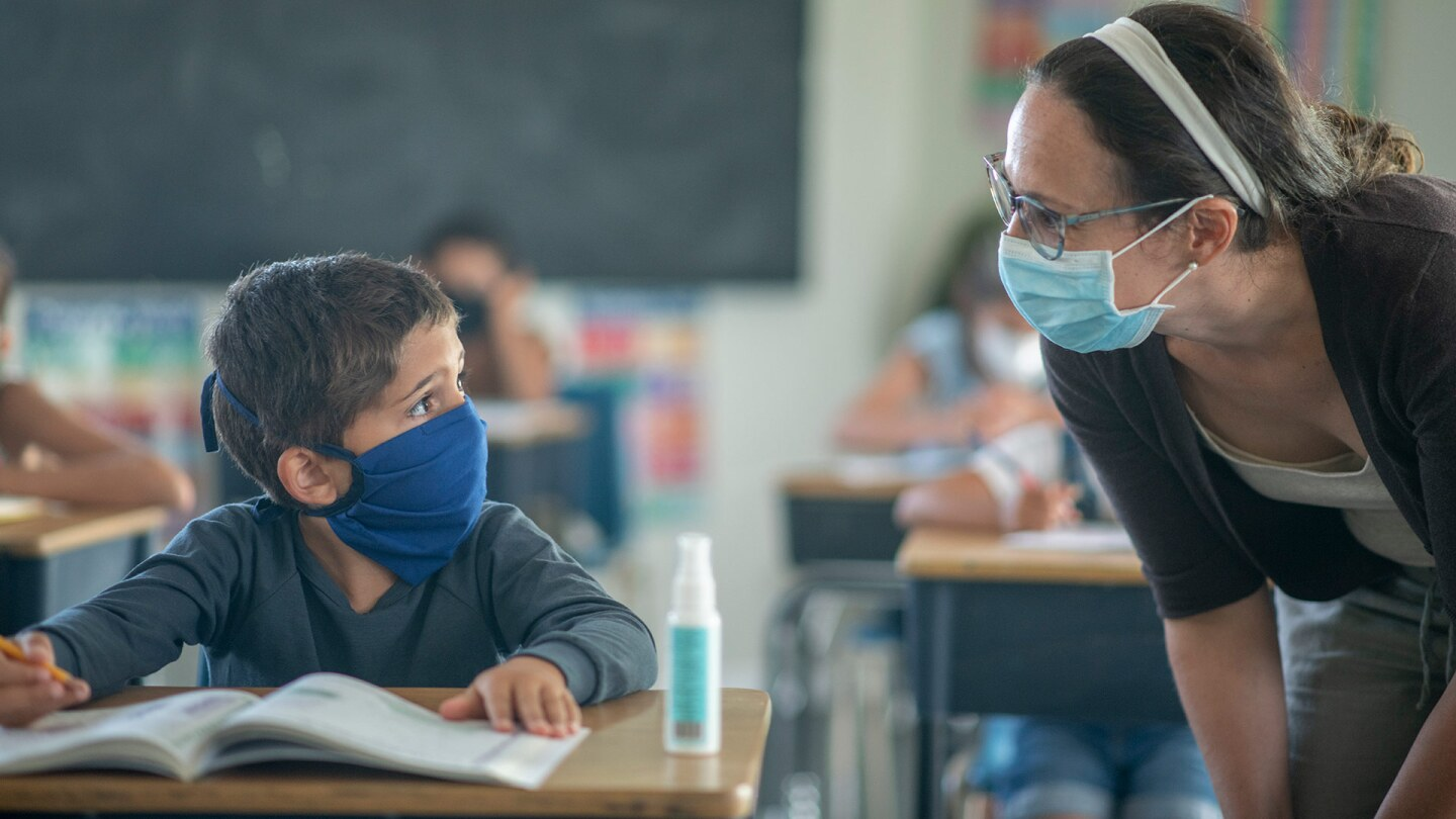 A masked teacher helps a small masked child. istock