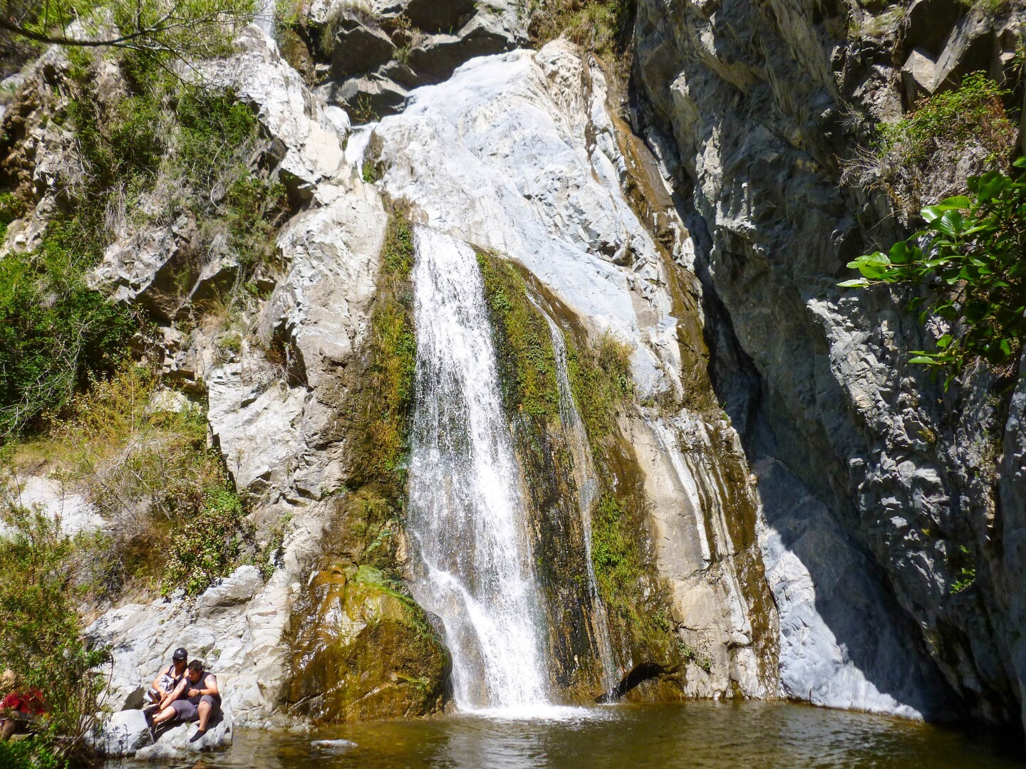 The waterfall at Fish Creek in Angeles National Forest. At the bottom left corner of the photograph are two hikers resting by the creek.