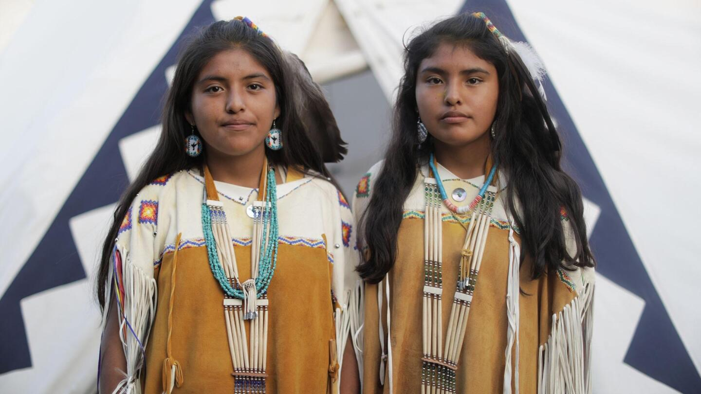 """Two young girls wearing traditional clothing stand side by side for a picture. 