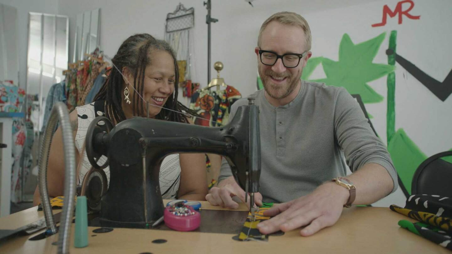 "Nathan sewing a doll dress at Irie Vibes | Still from ""Lost LA"" Shindana Toys"