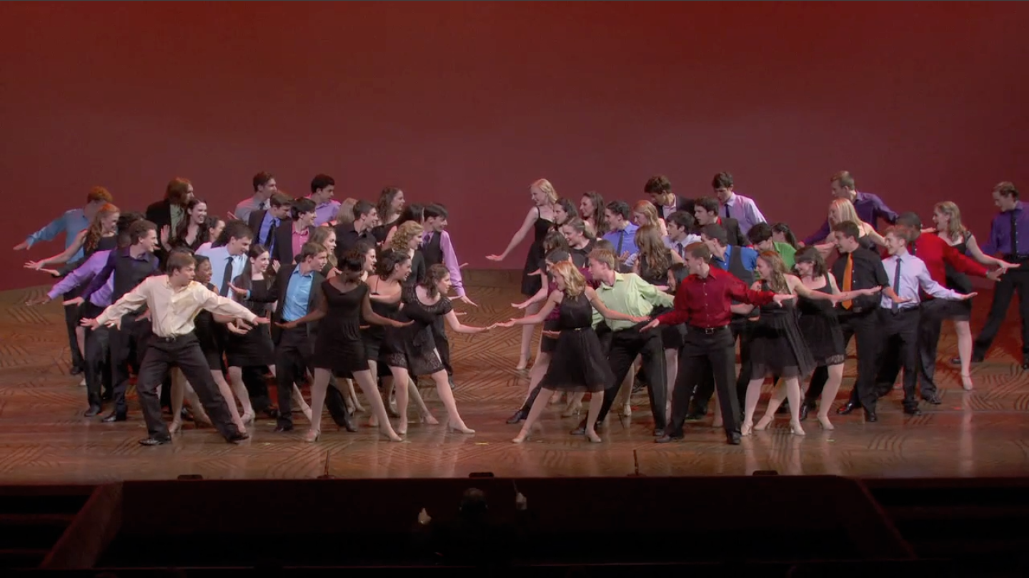 Many performers on stage in the middle of performing a dance number.