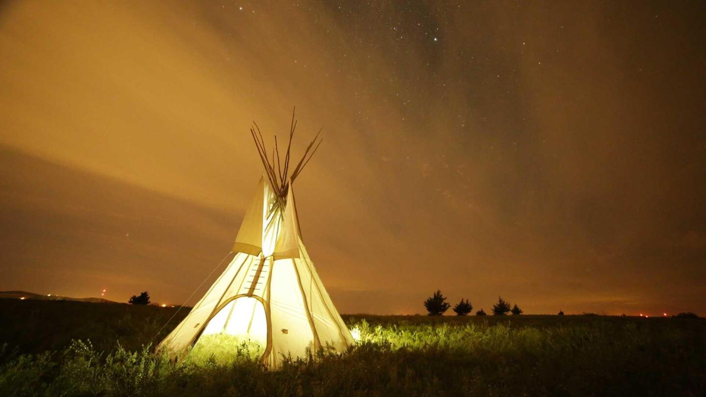 "A Native American teepee is lit up against a vast, empty field. | ""Native America: New World Rising"""