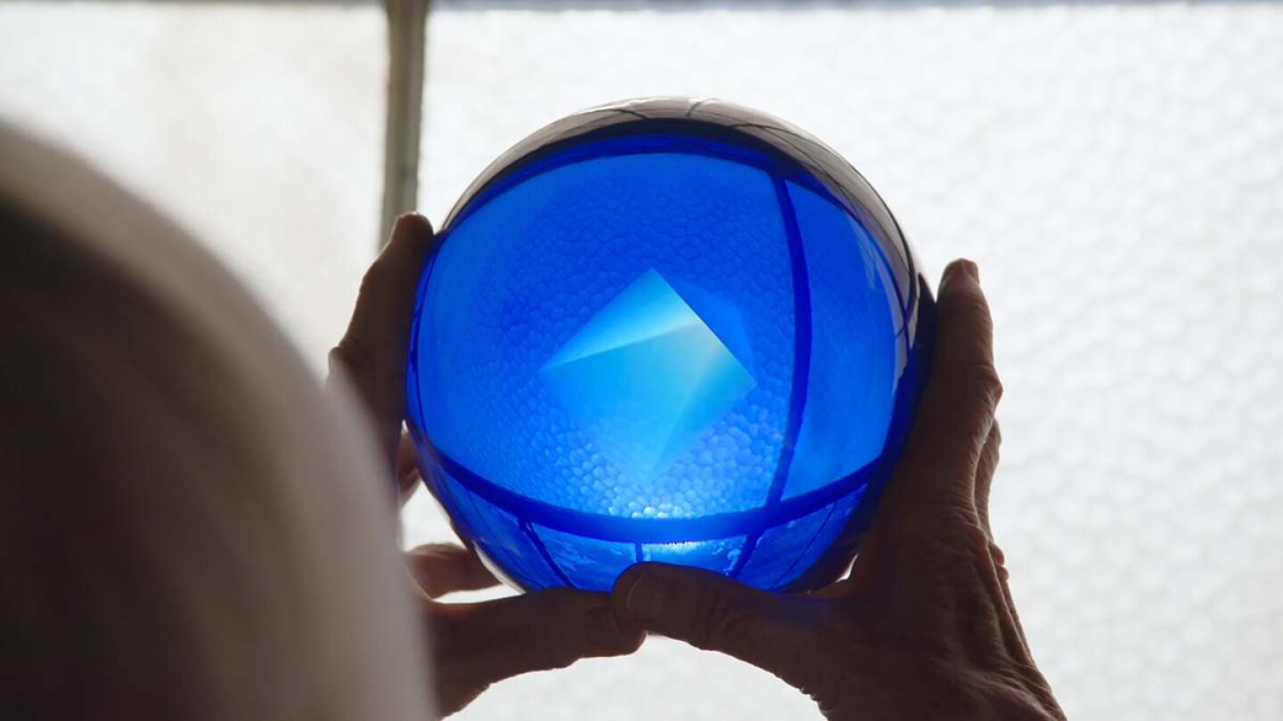 A pair of hands holding up a shining blue sphere.