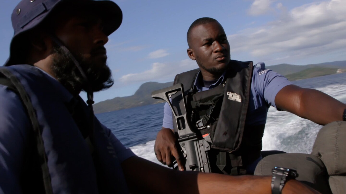 "Two men stand on a boat, with one of them handling a rifle. | From ""Foreign Correspondent: Pirates of the Caribbean"""